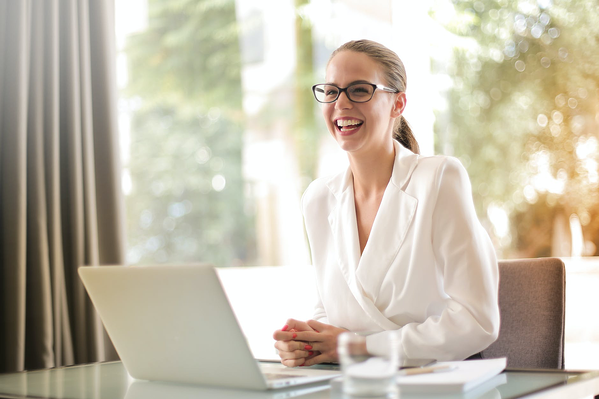 Laughing business woman in office with laptop