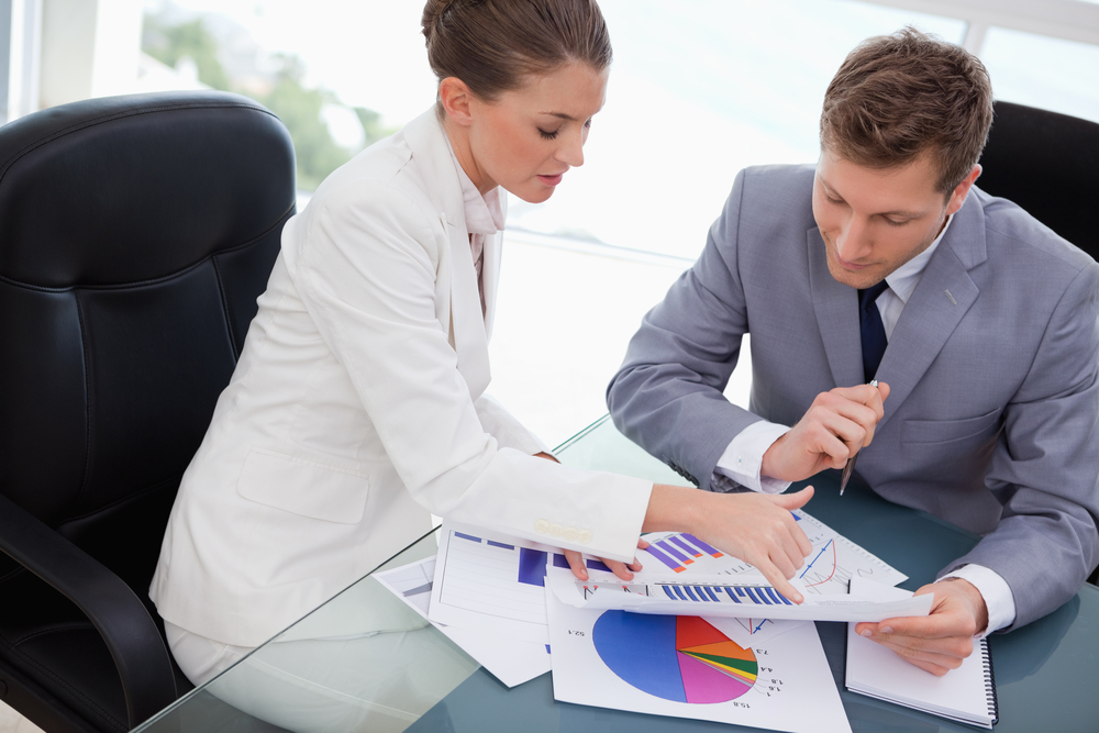 Woman helping man with accounting
